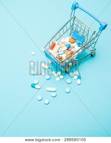 Pills And Shopping Trolley On Blue Background. Creative Idea For Health Care Cost, Drugstore, Health
