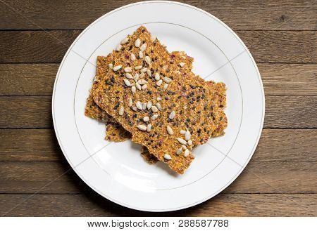 Dehydrated Raw Vegan Bread On White Plate On Brown Wooden Table. Top View Background. Close Up. Cent