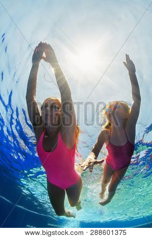 Happy Family - Young Mother, Girl Learn To Swim And Dive Underwater. Jump With Fun In Swimming Pool.