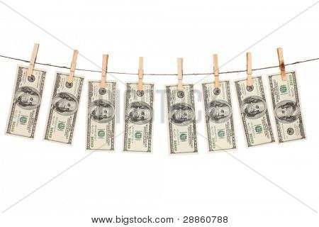 Alot of one hundred dollar bills is hanging on a rope with wooden clothespin isolated on white