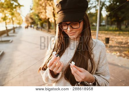 Beautiful Young Girl Holding Wireless Headphones In Park