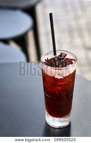 Cherish cocktail drink with dark straw on black table outdoors poster