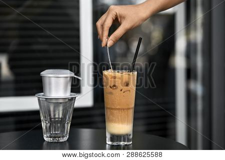 Woman Stirs Iced Coffee Drink With Spoon In Outdoor Cafe