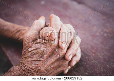 Hands Asian elderly woman grasps her hand on lap, pair of elderly wrinkled hands in prayer and Traces of work hard , World Kindness older and Adult care, Mother day people and older insurance concept poster