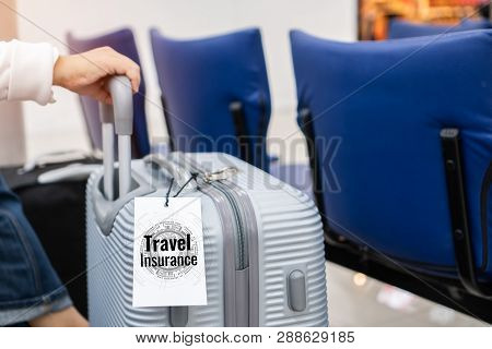Tourist Traveler With Travel Insurance Tag Suitcase Baggage Put Letter