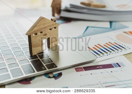 Property Real Estate Mortgage Loan Or Investment Concept: Wooden Home Model On Computer With Chart R