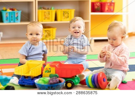 Nursery Babies Girl And Boys Playing Together In Playroom In Kindergarten