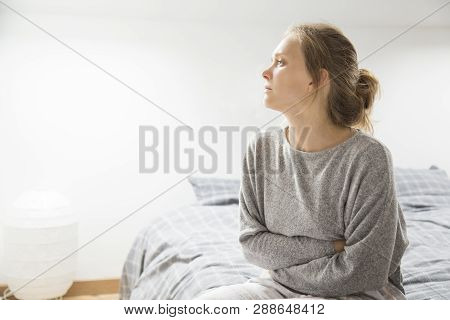 Sad Stressed Girl Suffering From Stomach Pain. Young Woman Sitting On Bed And Covering Belly With Ha