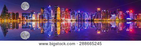 Banner Panorama Of Doha West Bay Skyline Lighting By Night Reflecting In Doha Bay. Modern Skyscraper