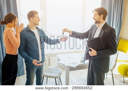 Couple Buy Or Rent Apartment Together. Realtor Give Keys To Young Man. Woman Happy Enjoying. New Lif