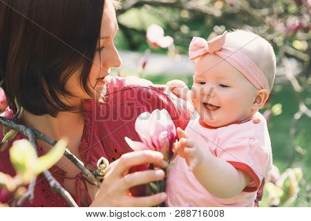 Loving Mother And Baby Girl Are Smelling Blooming Blossom Pink Magnolia Tree. Young Beautiful Mom An
