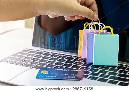 Carrying Paper Shopping Bag With Finger And Mock Up Of Credit Card On Laptop Keyboard. Consumer Can