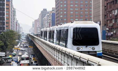 Mass Rapid Transit (mrt) Train On The Rail Track With Modern Building In The City, Transportation In
