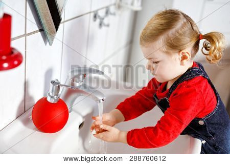 Cute Little Toddler Girl Washing Hands With Soap And Water In Bathroom. Adorable Child Learning Clea
