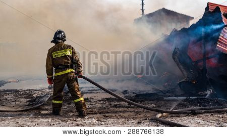 Firemen Extinguishes A Burning Old Wooden Residential House, Tyumen, Russia: March 2, 2019. Firefigh