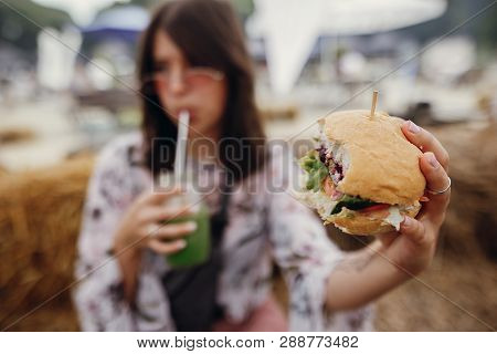Stylish Hipster Girl Holding Delicious Vegan Burger And Smoothie In Glass Jar In Hands At Street Foo