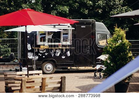 Food Van Truck. Stylish Black Mobile Food Truck With Burgers And Asian Food At Street Food Festival.