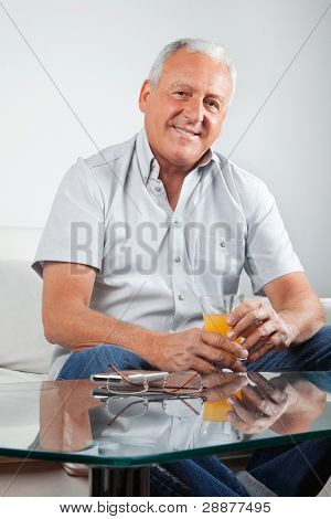 Portrait of casual senior man holding glass of orange juice