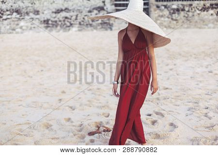 Beautiful elegant young lady in bohemian straw hat and red maxi dress walking on sandy beach