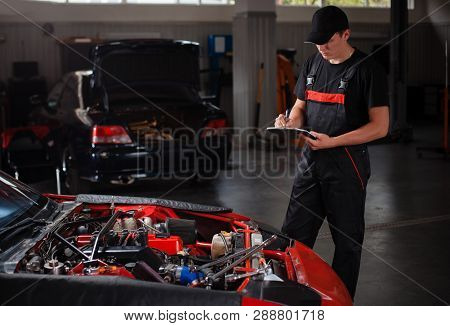 A Serviceman With Wrench, Make A Test.     There Is A Car In The Background.