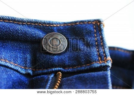 Button On Blue Denim Jeans Front Isolated On Empty White Background. Classic Simple Rivet And Blue J