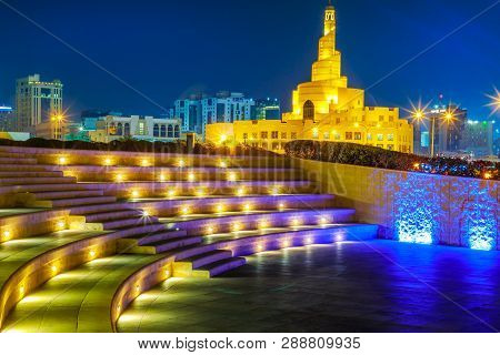 Stairs Of Small Amphitheater At Souq Waqif Garden Near Doha Corniche With Doha Mosque At Night. Doha