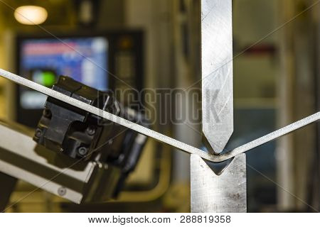 Hand Robot Working Automatic Cutting And Bending Metal Sheet. Operator Bending Metal Sheet By Sheet