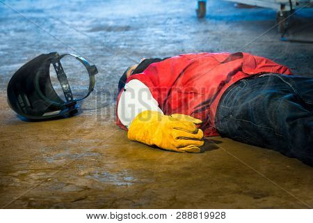 Welder Accident In Works And Fainting In A Factory Industrial. Safety And Protection Equipment In Wo