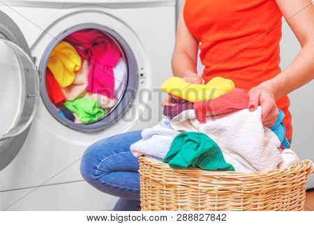Laundry. Young Woman Loads The Laundry In The Washing Machine From The Laundry Basket Before Washing