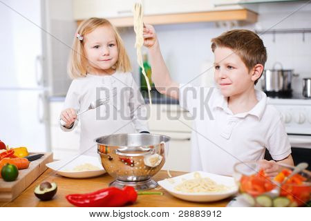Two kids at kitchen eating spaghetti