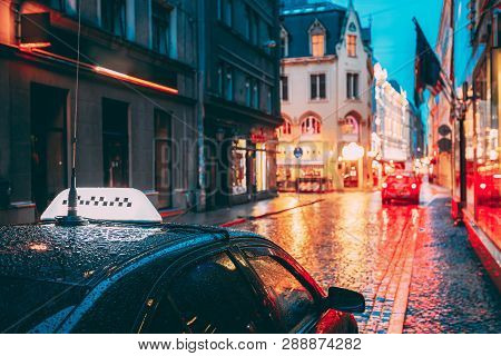 Taxi Car Wait Clients Near Cafe In Old European Streets In Rainy Evening. Night Street Illuminations