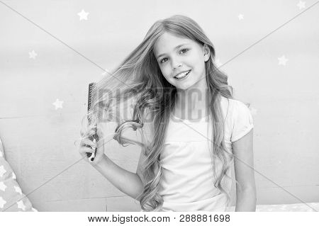 Child curly hairstyle hold hairbrush or comb. Comb hair before go to sleep. Hairdressing habits concept. Conditioner or mask organic oil comb hair. Girl long curly hair bedroom interior background. poster