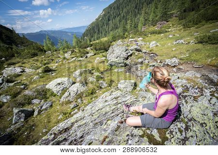 Enjoying The Idyllic Mountain Landscape: Girl Is Sitting On A Rock And Resting