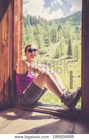 Young Woman With Alpine Boots And In Sports Wear Is Sitting In The Door Of A Mountain Chalet And Enj