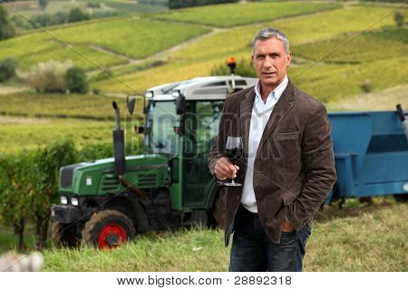 Winemaker tasting a glass of wine in a vineyard