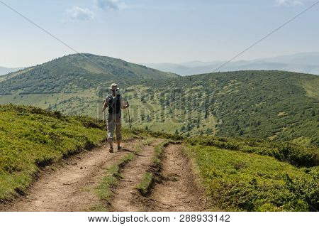 The Young Woman With A Backpack And Ski Poles Walking Uphill To Peak Of The Mountain. Travel Adventu