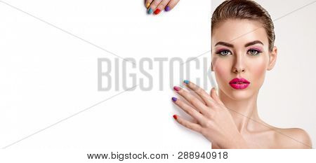 Beautiful  woman with a colored manicure holds blank poster. Attractive white girl with empty billboard. Glamour fashion model's holding placard, free space. Fashionable  advertisment concept. Art