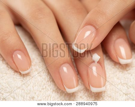 Woman applies a cosmetic moisturizer on her hands. Beautiful female hands. Woman gets manicure procedure in a spa salon. Hand care. Woman cares for the hands. Beauty treatment with skin of hand.