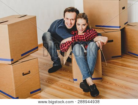 Woman sitting in cardboard for fun. Young couple moving on to new flat.
