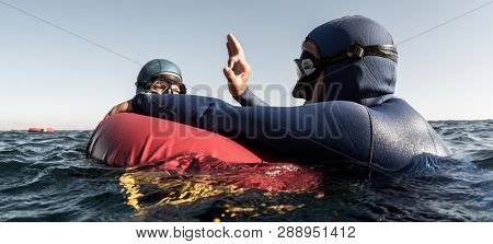 Freediver performs consciousness check on the buoy and shows Ok sign to the buddy after deep dive