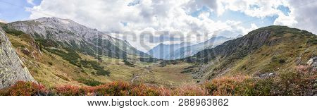 Alpine Landscape: Meadow, Mountains And Blue Sky
