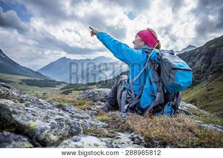 Woman In Sportswear And With Backpack Is Sitting On The Stony Ground And Points Somewhere