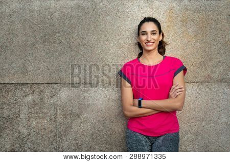 Smiling sporty young woman take a break after running. Confident latin girl leaning against wall in sportswear. Portrait of happy runner looking at camera and smiling with crossed arms, copy space.