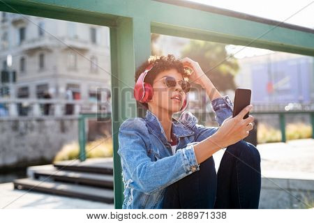 Young african woman listening to music with headphones on street. Portrait of brazilian girl listening music online with wireless headphone from a smartphone. Urban girl enjoy songs on the ground.