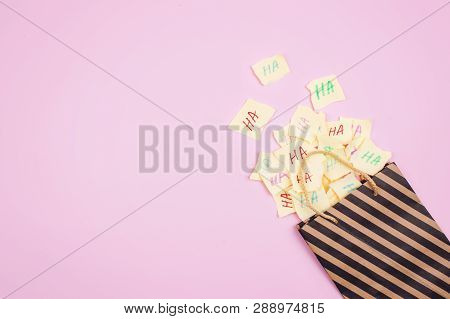 April Fools' Day Celebration Background. Paper Bag With Many Paper Sheets With The Words Haha. 1 Apr