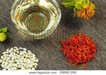 Safflower. Oil, Seeds, Bud, Flower, Red Inflorescences Of Wild Saffron. Close-up, Gray Woven Backgro