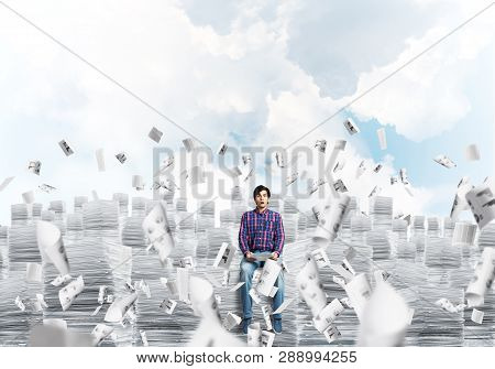 Young Man In Casual Clothing Sitting On Pile Of Documents Among Flying Papers With Cloudly Skyscape