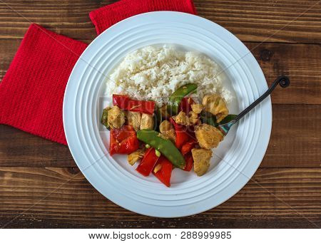 Plate with chicken, rice and vegetables directly from above on wooden background