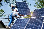 Two workers mounting heavy solar photo voltaic panel on tall steel platform on green tree and blue sky background. Exterior stand-alone solar panel system installation, dangerous job concept. poster