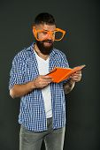 Self education concept. Literary club. Reading book as hobby. Study is fun. Hipster bearded man funny eyeglasses hold notepad or book. Read this book. Comic and humor sense. Courses adult education. poster
